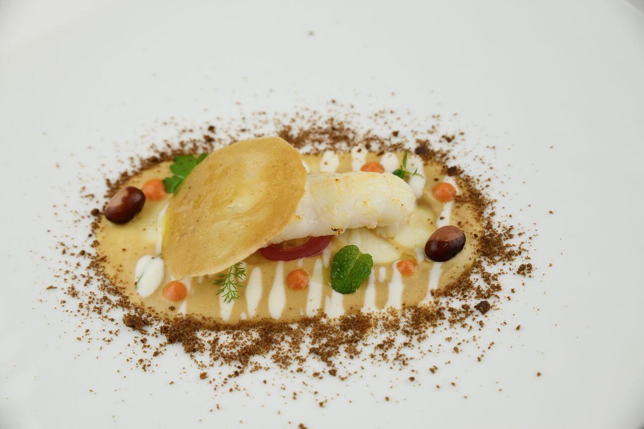 Scampo scottato servito su una crema di fasola Badda con ricotta, quinoa soffiata e granita d'acciuga